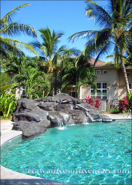Pool with lava rock waterfall at one end with Hawaiian style 2 story buildings around it
