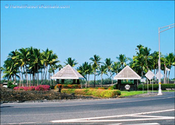 Waikoloa Beach entry with 2 light gray gazebos on either side Waikoloa Beach Drive
