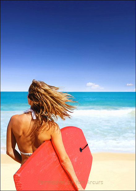 Blonde surfer girl walking toward the ocean with red boogie board under her arm