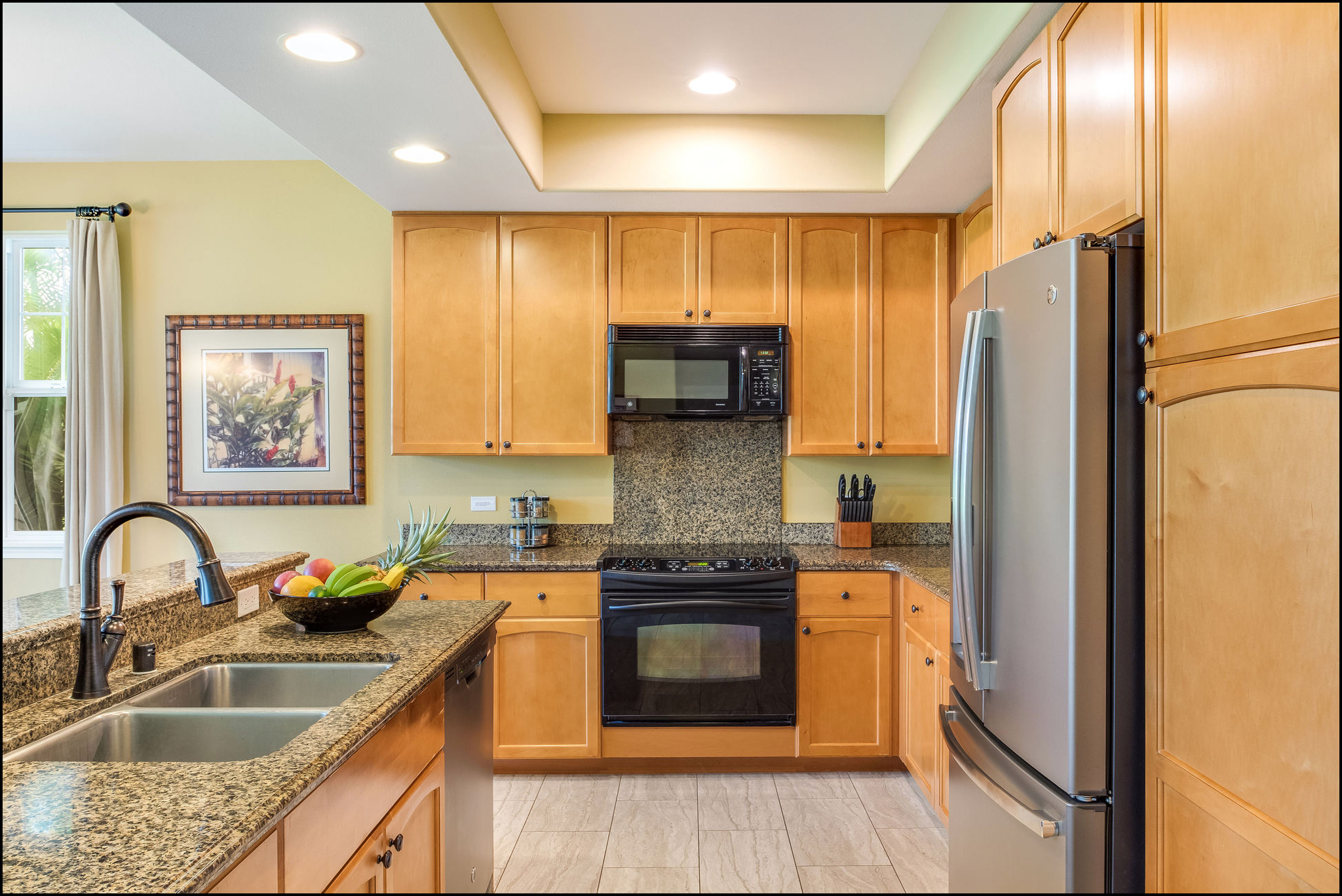 Kitchen with center island with sink, side-by-side fridge, electric cooktop stove, granite counters and maple cabinets
