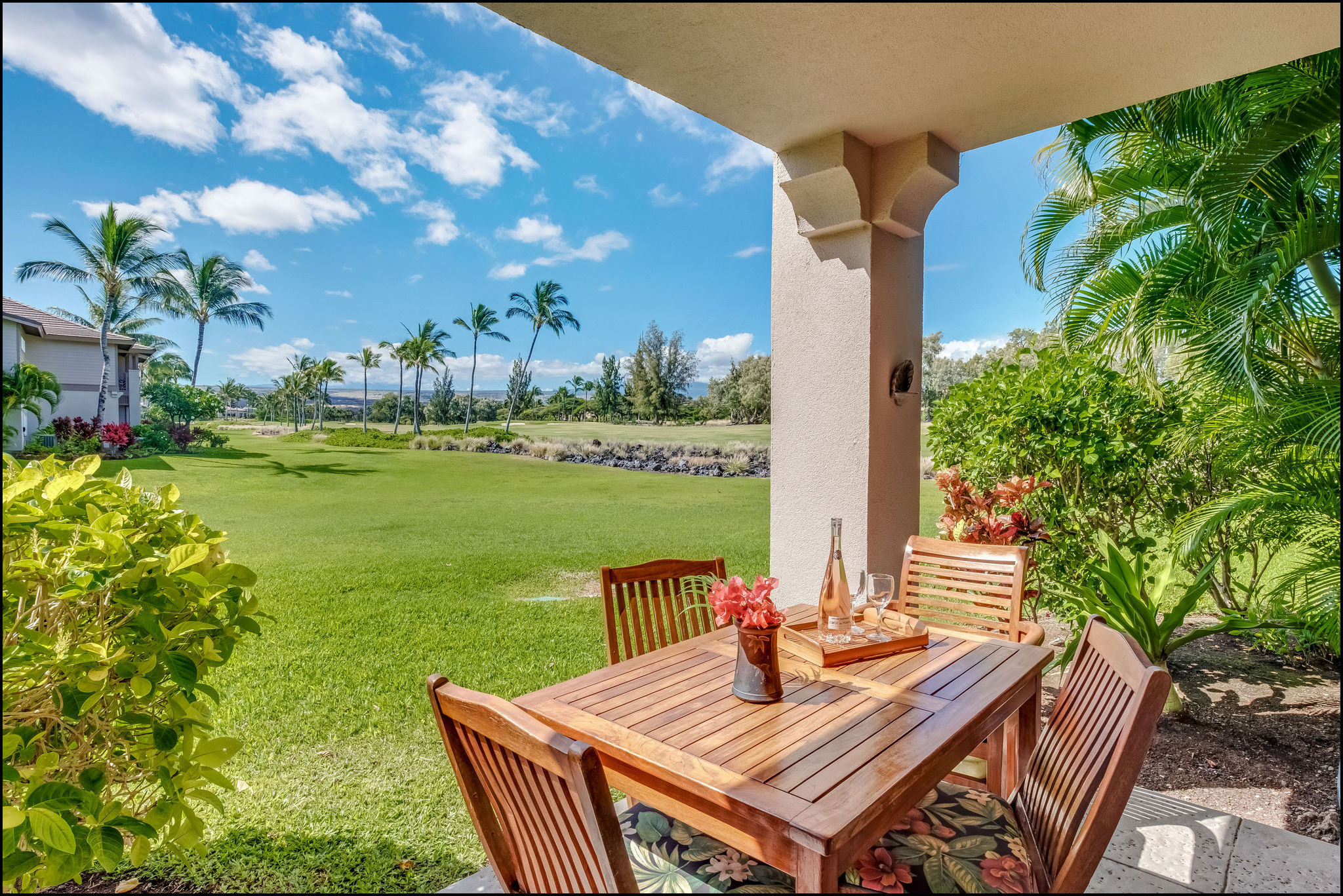 Lanai with one step down to luxurious lawn and landscaping including palms, fragrant flowering trees, and red ginger