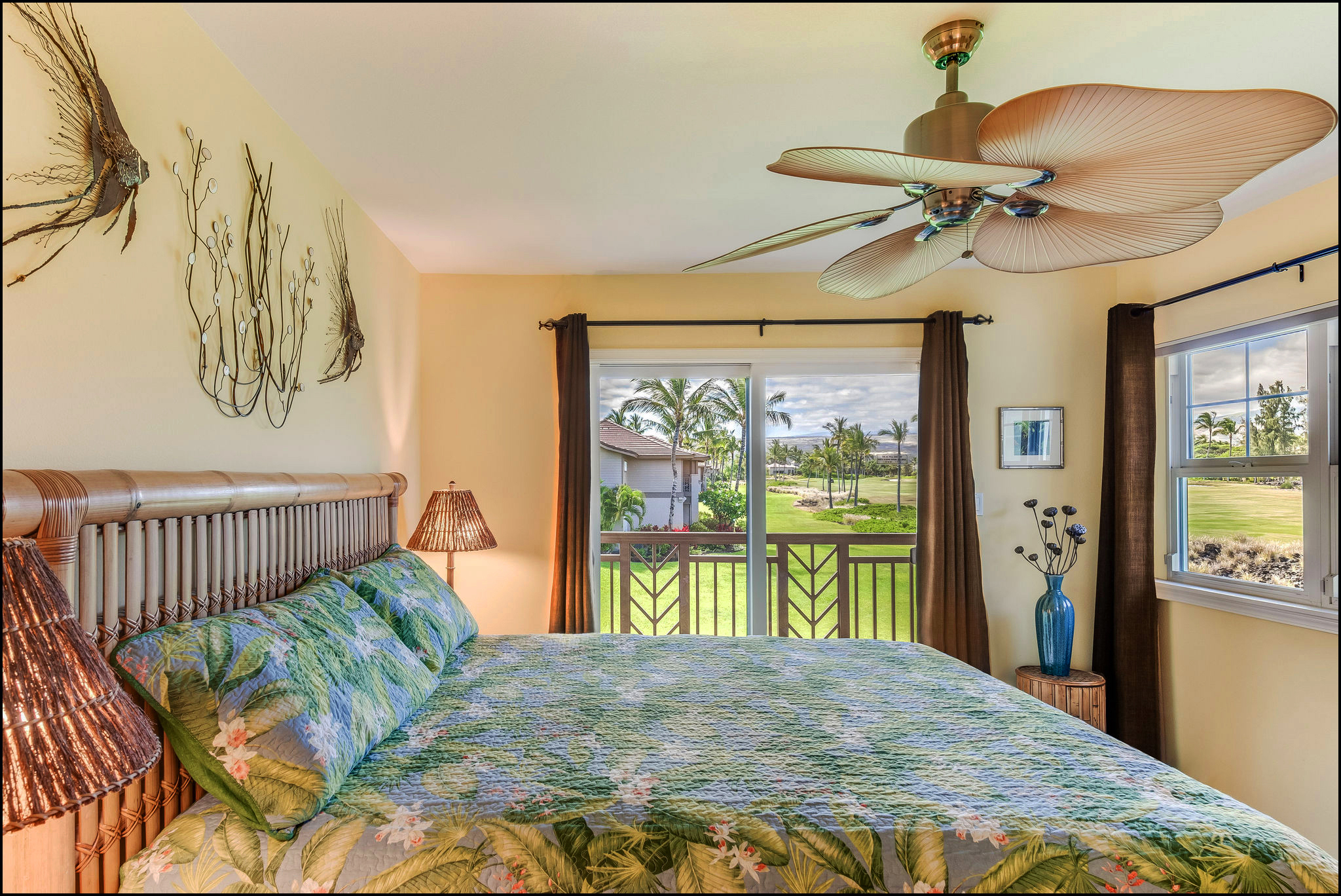 Private second floor master bedroom with big green views furnished with handsome bamboo furniture, a ceiling fan and a small lanai