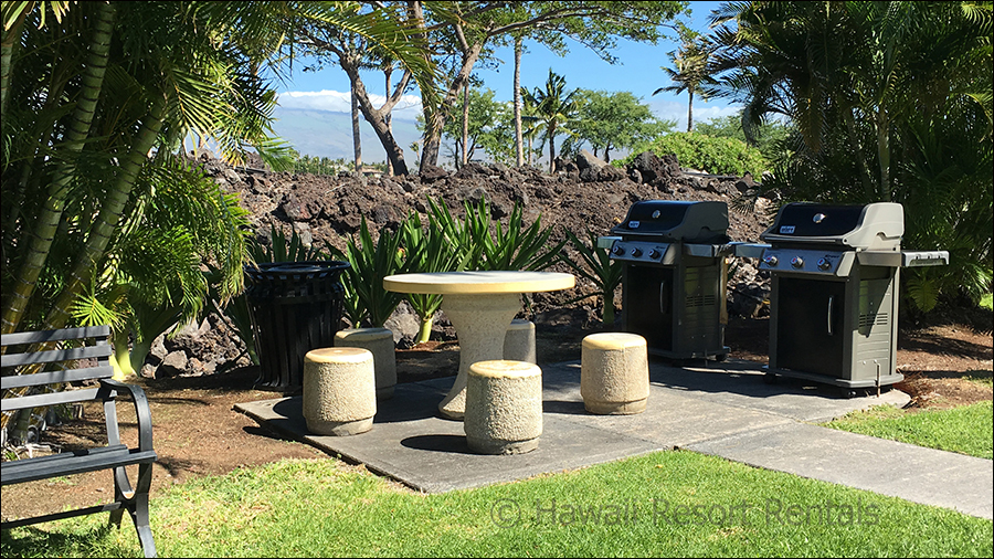 Waikoloa Colony Villa's outdoor stone table and chairs beside two gas BBQ grills surrounded by tropical vegetation