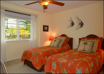 Second bedroom has 2 twin beds with colorful Hawaiian patchwork quilts and ceiling fan. A window overlooks palms and black lava fields