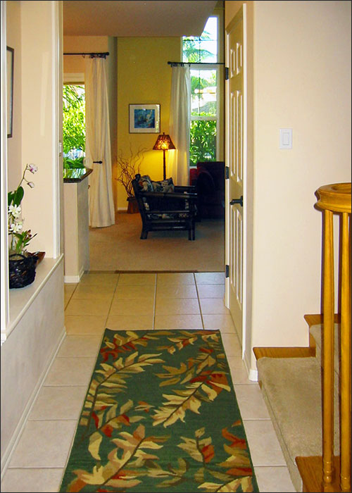 Hale Wailele's inviting entry shows Hawaiian plants growing outside with a view through the hall to the living room and view of the pool beyond